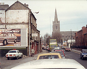 Picture taken circa 1988. Scene shows traffic heading toward Dublin city centre along New Street. St Patricks Cathedral  is shown up ahead on the right. The cathedral is one of the many tourist attractions in Dublin. Founded in 1191 it is the national cathedral for the Church of Ireland.<br /> <br /> <br /> <br /> Old amateur photos of Dublin streets churches, cars, lanes, roads, shops schools, hospitals, Streetscape views are hard to come by while the quality is not always the best in this collection they do capture Dublin streets not often available and have seen a lot of change since photos were taken Old Fire, Blackrock, Library, Bookshop, Carraig Books, St Patrick's Cathedral from Clanbrassil st April 1984