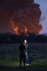 "© Licensed to London News Pictures . 15/03/2015 . Salford , UK . People pose for a selfie with the fire burning behind . Roads are closed and people have been evacuated as a large fire burns at a unit within "" Junction Eco-Park "" in Clifton , Greater Manchester , this evening (Sunday 15th March 2015) . The smoke and flames can be seen for many miles . Forty fire fighters are at the scene working to control the blaze . Photo credit : Joel Goodman/LNP"