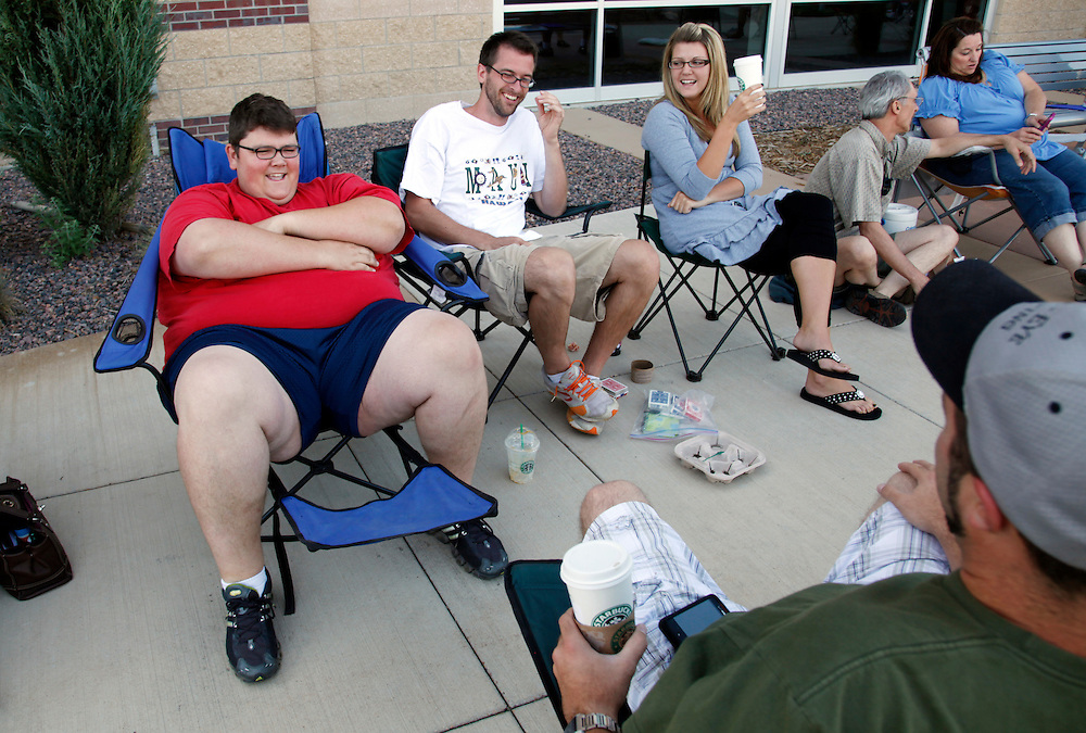 """Greg Marthaler (L) waits in line with friends and family for an open casting session for season 11 of """"The Biggest Loser"""" television show studies the application for the show in Broomfield, Colorado July 17, 2010. Over 600 people, many spending the night on the sidewalk outside the hall applied for a chance to be on the show and win $250,000.  REUTERS/Rick Wilking (UNITED STATES)"""