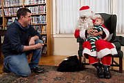 As Santa, Euclid Farnham meets with children at the Tunbridge Public Library in Tunbridge, Vt., on Dec. 8, 2018. Profits from sales to benefit the library. (Photo by Geoff Hansen)
