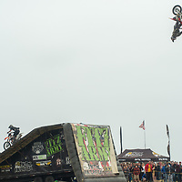 Stunt motorcyclists fly off a jump at Dream Machines, Half Moon Bay Airport, California.