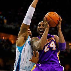 Mar 29, 2010; New Orleans, LA, USA; Los Angeles Lakers guard Kobe Bryant (24) shoots and draws a foul from New Orleans Hornets forward David West (30) during the second half at the New Orleans Arena. The Hornets defeated the Lakers 108-100. Mandatory Credit: Derick E. Hingle-US PRESSWIRE