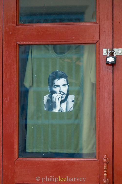 Portrait of Che Guevara on t-shirt hanging behind window, Havana, Cuba