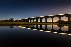 © Licensed to London News Pictures. 01/02/2021. Arthington UK. A commuter train leaves a light trail as it crosses Arthington viaduct near Otley in Yorkshire this morning. Photo credit: Andrew McCaren/LNP