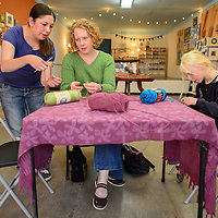 051414       Cable Hoover<br /> <br /> Instructor Brandy Lee, left, shows Leslie Norton and Heidi Norton how to start a crochet chain during a class at Makeshift Gallery in downtown Gallup Wednesday.
