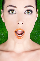 Closeup portrait of a beautiful surprised woman with wide open green eyes and glossy lips on green