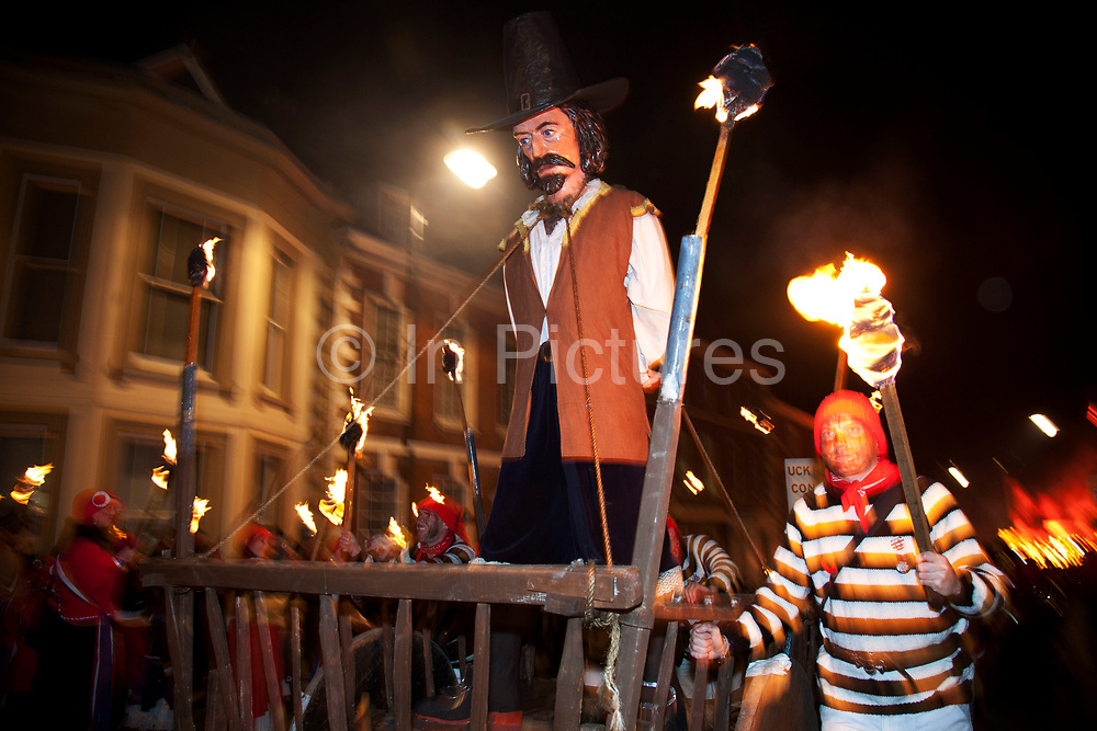 Lewes, UK. Monday 5th November 2012. Cliffe bonfire society members carry an effigy of Guy Fawkes. Bonfire Night celebration in the town of Lewes, East Sussex, UK which form the largest and most famous Guy Fawkes Night festivities. Held on 5 November, the event not only marks the date of the uncovering of the Gunpowder Treason and Plot in 1605, but also commemorates the memory of the 17 Protestant martyrs from the town burnt at the stake for their faith during the Marian Persecutions of 1555–57. There are six bonfire societies putting on parades involving some 3,000 people.