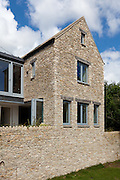 Quince Tree Cottage, Rockness, Gloucestershire. Architect: Millar Howard Workshop 2009. A large extension to an old cotswold cottage. The idea was to build a new cotswold stone building next to the original house and join the new and the old with a glazed link. rather than try and match the stone of the original it was decided to build the new extension with a drystone facing to contrast the new and the old. Sliding folding doors open at a corner to allow the kitchen/dining room to spill out into the garden.