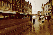 People walk along the tram tracks in the old town of Ghent on a wet September afternoon