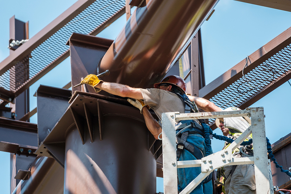 Greg Gentry, left and Rick Handy, work from a bucket high above the ground to secure the billboard structure to it's base as technicians from Lamar Advertising install a digital billboard structure along Wards Road in Lynchburg, VA Wednesday, August 29, 2018. U.S. companies are investing in re-training efforts to fill a slew of open positions as a tight labor market and changing job requirements makes it hard to find qualified staffers.<br /> CREDIT: Justin Ide for The Wall Street Journal<br /> RETRAIN