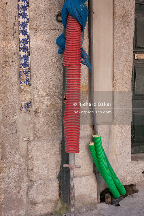 Construction sleeves protecting drainpipes outside a home in Porto, Portugal.