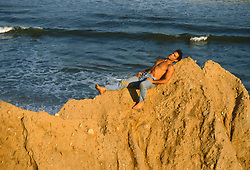 Hunky man resting on a cliff in Montauk, NY