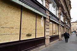 Edinburgh, Scotland, UK. 18 April 2020. Views of empty streets and members of the public outside on another Saturday during the coronavirus lockdown in Edinburgh. Prince Brasserie in Balmoral Hotel closed and windows boarded up.  Iain Masterton/Alamy Live News