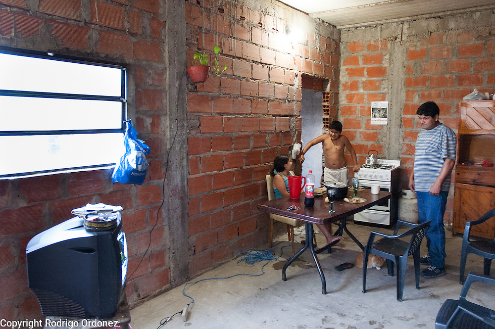 A family watches television at their home in Ocho de Mayo.