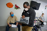 Kyle Horton, BS, Neonatal Resuscitation Program, center, looks up information on a laptop, as Lehigh Valley Health Network brought their mobile vaccination clinic to Majestic House on May 6, 2021, which offers low income housing to Seniors 55 years and over, in Tamaqua, Pennsylvania.