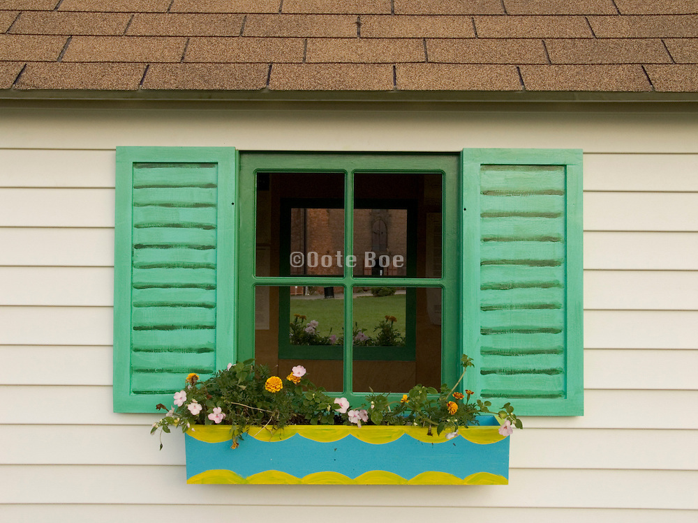 idyllic window of small shed with painted shutters and flower box