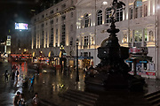 Seen from a London bus on a rainy night in the West End, night visitors stand beneath the statue to Eros in Piccadilly Circus, on 27th August 2020, in London, England.