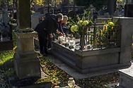 A couple lights a candle at Rakowicki cemetery in Krakow, Poland 2019.