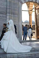 A bride and groom doing wedding photos walk out an entrance to the Süleymaniye Mosque in Istanbul, Turkey. The mosque was built between 1550 and 1557.