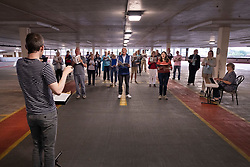 © Licensed to London News Pictures. 23/06/2021. Epsom, UK. Musical Director Julian Collings (L) rehearses Epsom Choral Society in a multi-storey car park in Epsom, Surrey. The choir, in it's 99th year, has resorted to rehearsing in a socially distanced way on the 4th floor of the Ashley Shopping Centre car park after government Covid-19 regulations were updated to say that amateur choirs are only allowed to gather in groups of six indoors. Epsom and Ewell Borough Council agreed to the use of the car park which allows the choral society to rehearse in two groups of 30 outdoors but sheltered from the elements. Photo credit: Peter Macdiarmid/LNP