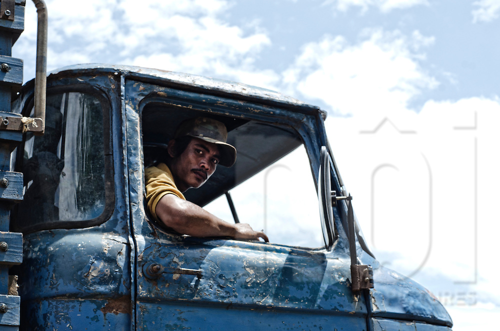 A Laotian trucker looks out the open window of his old blue truck in Sekong Province, Laos, Southeast Asia