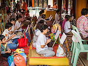 """10 AUGUST 2014 - BANGKOK, THAILAND: Women pray during a Ghost Month service to venerate ancestors at Wat Mangkon Kamalawat, the largest Mahayana Buddhist temple in Bangkok's Chinatown. The seventh month of the Chinese Lunar calendar is called """"Ghost Month"""" during which ghosts and spirits, including those of the deceased ancestors, come out from the lower realm. It is common for Chinese people to make merit during the month by burning """"hell money"""" and presenting food to the ghosts.      PHOTO BY JACK KURTZ"""