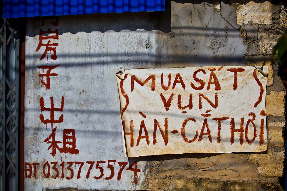 """A sign that says """"room for rent"""" in Chinese is seen along with Vietnamese sign near the Haiphong Thermal Power Plant construction site in Trung Son, Vietnam, Nov. 22, 2009. At the construction site here, a few miles northeast of the port city of Haiphong, an entire Chinese world has sprung up, including four walled dormitory compounds for the Chinese workers, restaurants with Chinese signs advertising dumplings and fried rice, and currency exchange shops."""