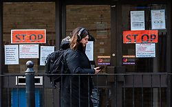 © Licensed to London News Pictures. 15/03/2020. London, UK. A woman walks past 'STOP' signs on the door of Wapping Health Centre in east London. Wapping Health Centre has announced that from Monday 16th March, all new appointments at the GP surgery will be made by telephone triage only, to minimise cross infection and protect their medical workforce from coronavirus and has stated that any patients with pre-booked appointments next week should not come into the surgery but instead wait for a telephone call from their doctor. Photo credit: Vickie Flores/LNP