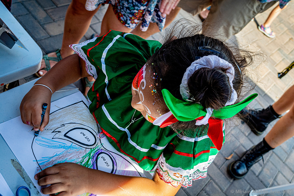 Little Latina wearing traditional Mexican dress is coloring a paper Luchador mask during the 2019 Iowa City Latino festival.