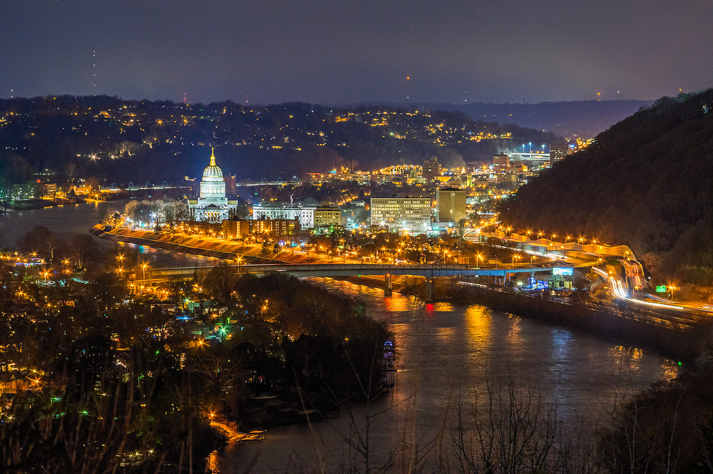 City lights reflect off the Kanawha River at night leading to the Capitol Building of Charleston, West Virginia.