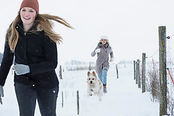 Teenage girls running with dog in snowfield, Bavaria, Germany