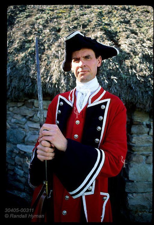 Man dressed as Redcoat poses outside Old Leanach Cottage, only building left standing from the Culloden battle of 1746; Scotland.