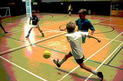 Group of boys playing football in school sports hall during physical education lesson,