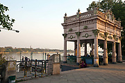Two women sit by the pier on the Strand by the Hoogley River, Chandannagar, India