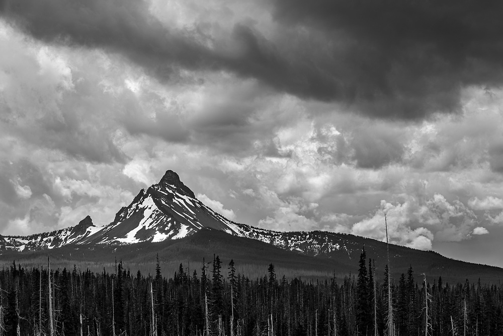Afternoon thunderstorm clouds rise above Mount Washington in the Cascade Range of Oregon.