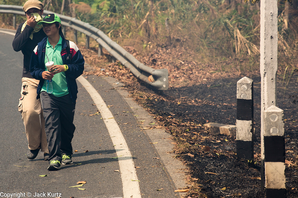 "06 APRIL 2013 - CHIANG MAI, CHIANG MAI, THAILAND: Hikers cover their faces because of the smoke as they walk past an illegal burn on the edge of Chiang Mai. The ""burning season,"" which roughly goes from late February to late April, is when farmers in northern Thailand burn the dead grass and last year's stubble out of their fields. The burning creates clouds of smoke that causes breathing problems, reduces visibility and contributes to global warming. The Thai government has banned the burning and is making an effort to control it, but the farmers think it replenishes their soil (they use the ash as fertilizer) and it's cheaper than ploughing the weeds under.   PHOTO BY JACK KURTZ"