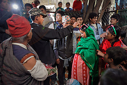 Durga, 16, applies sindoor, or vermillion powder, to his young bride Niruta's part during their wedding ceremony in Kagati village Nepal on Jan. 23, 2007, which was the auspicious day of Vasant Panchami, a Hindu holiday celebrating the coming of spring. Niruta, 14, was nine-months pregnant during the ceremony, attended by friends and relatives. Durga's father hadn't liked the idea of his son abandoning his education and marrying young, but after Durga's mother's death, the family desperately needed help in both the home and the fields. So they found a suitable young bride.<br /> <br /> The 2015 earthquakes devastated Nepal and left girls and women in an increasingly vulnerable position, leading experts to believe child marriage rates will increase over the coming years.