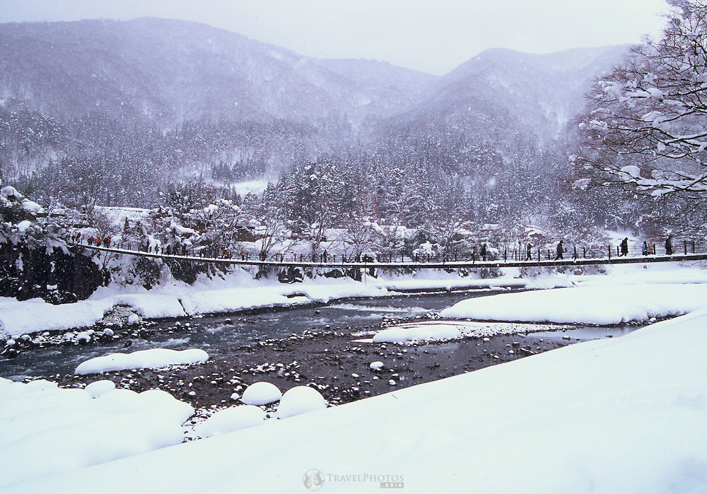 Snowy scenes showing tourists at a village of traditional Japanese rural architecture.