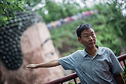 A Chinese man poses in front of the giant Buddha (Chinese: 樂山大佛 ; Lèshān Dàfó) in Leshan, China, August 09, 2014.<br /> <br /> Confucianism, Taoism and Buddhism are the three major religions in China. Temples and statues witness their ancient roots all over the Chinese country.<br /> <br /> © Giorgio Perottino
