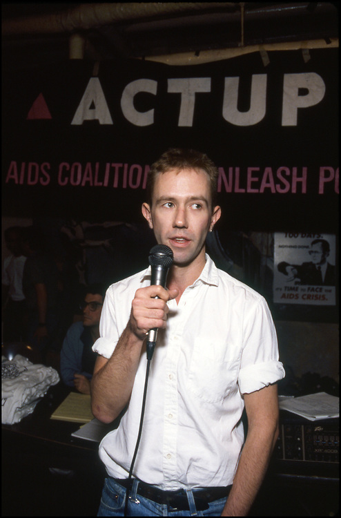 Mark Harrington of the AIDS Coalition To Unleash Power (ACT UP) and the Treatment Action Group (TAG) speaks to the floor at an ACTUP meeting at The Center in New York City in 1990.