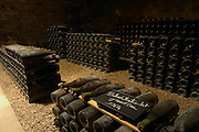 In the underground wine cellar: a pile of bottles of Batard Montrachet Grand Cru 1964 red Burgundy wine with the appellation written in white text on a black chalkboard chalk board on a gravelly pebbly soil, Maison Louis Jadot, Beaune Côte Cote d Or Bourgogne Burgundy Burgundian France French Europe European