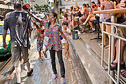 "Apr. 13, 2010 - Bangkok, Thailand: A Thai woman throws water at a tourist while he passes a bar during Songkran festivities on a soi off of Sukhumvit Rd in Bangkok Tuesday. Songkran is the Thai New Year's holiday, celebrated from April 13 - 15. This year's official celebrations have been cancelled because of the Red Shirt protests but Thais are still marking the holiday. It's one of the most popular holidays in Thailand. Songkran originally was celebrated only in the north of Thailand, and was adapted from the Indian Holi festival. Except the Thais throw water instead of colored powder. The throwing of water originated as a way to pay respect to people, by capturing the water after it had been poured over the Buddhas for cleansing and then using this ""blessed"" water to give good fortune to elders and family by gently pouring it on the shoulder. Among young people the holiday evolved to include dousing strangers with water to relieve the heat, since April is the hottest month in Thailand (temperatures can rise to over 100°F or 40°C on some days). This has further evolved into water fights and splashing water over people riding in vehicles. The water is meant as a symbol of washing all of the bad away and is sometimes filled with fragrant herbs when celebrated in the traditional manner. Photo by Jack Kurtz"