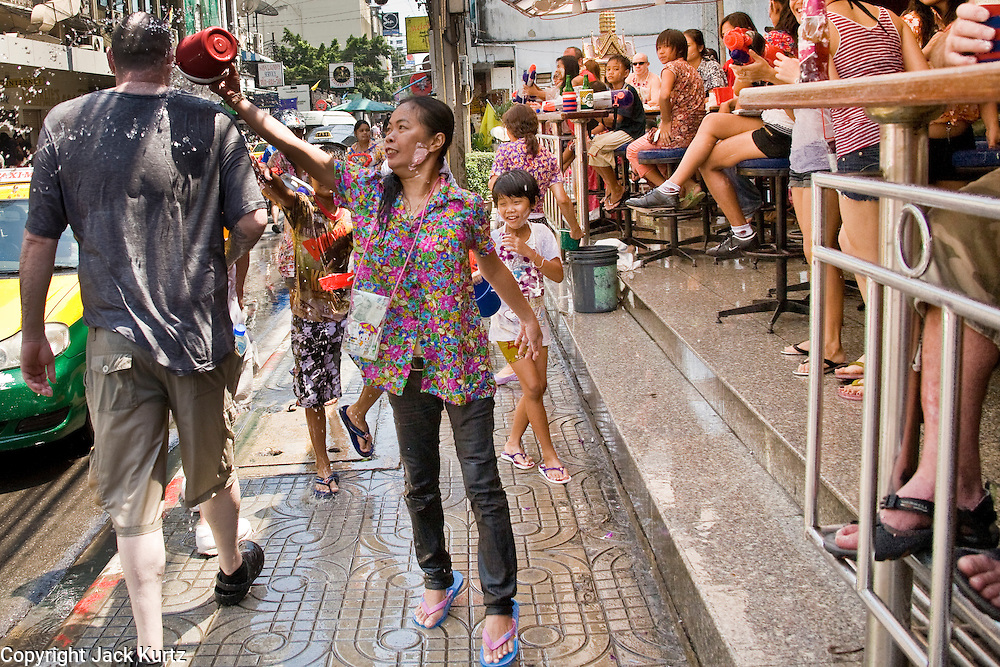 """Apr. 13, 2010 - Bangkok, Thailand: A Thai woman throws water at a tourist while he passes a bar during Songkran festivities on a soi off of Sukhumvit Rd in Bangkok Tuesday. Songkran is the Thai New Year's holiday, celebrated from April 13 - 15. This year's official celebrations have been cancelled because of the Red Shirt protests but Thais are still marking the holiday. It's one of the most popular holidays in Thailand. Songkran originally was celebrated only in the north of Thailand, and was adapted from the Indian Holi festival. Except the Thais throw water instead of colored powder. The throwing of water originated as a way to pay respect to people, by capturing the water after it had been poured over the Buddhas for cleansing and then using this """"blessed"""" water to give good fortune to elders and family by gently pouring it on the shoulder. Among young people the holiday evolved to include dousing strangers with water to relieve the heat, since April is the hottest month in Thailand (temperatures can rise to over 100°F or 40°C on some days). This has further evolved into water fights and splashing water over people riding in vehicles. The water is meant as a symbol of washing all of the bad away and is sometimes filled with fragrant herbs when celebrated in the traditional manner. Photo by Jack Kurtz"""