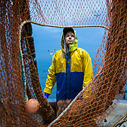 Luke guides the nets back onto the rigging to dry out after a night on the boat trawling.  Luke is a Folkestone based fisherman out trawling for a 12 hour night shift on a fishing trip in his boat Valentine FE20, Hythe Bay, the English Channel, United Kingdom.