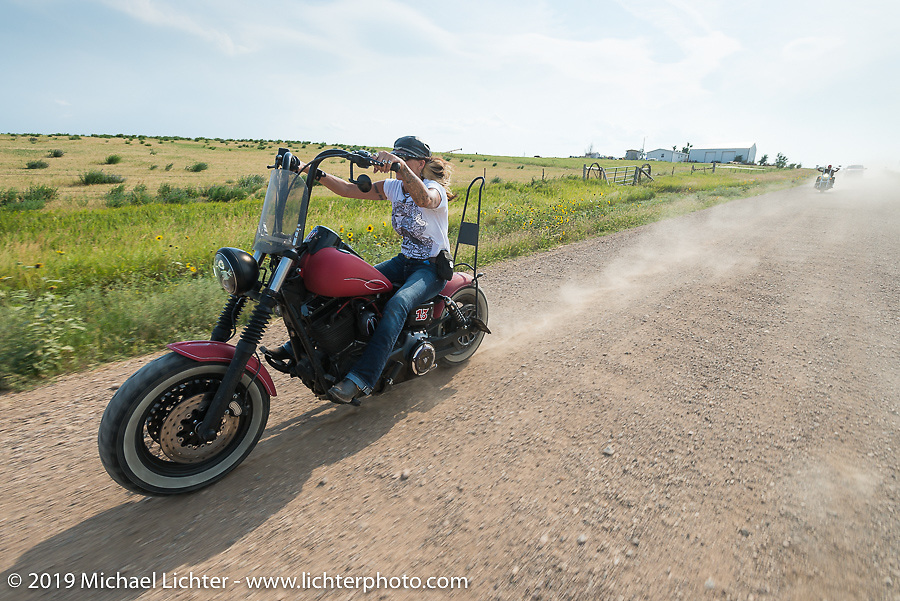 Debi Holmes takes the dirt back roads north of Sturgis to the Broken Spoke County Line during the Sturgis Black Hills Motorcycle Rally. SD, USA. August 4, 2014.  Photography ©2014 Michael Lichter.