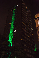 "London, UK. 14th June, 2018. The Green for Grenfell illuminations are lit at the Grenfell Tower and the twelve closest tower blocks (seen here Whitstable House on the Silchester East Estate) on the first anniversary of the fire in a display intended to 'shine a light"" of love and solidarity for all those affected and to raise awareness of the plight of those still without new homes after one year. Green for Grenfell is a community-led initiative in collaboration with tenants' and residents' associations and Grenfell United."