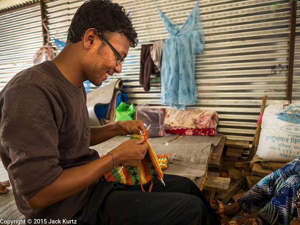 02 AUGUST 2015 - BHAKTAPUR, NEPAL:  A high school student makes woven hats for tourists in the sleeping quarters he shares with 35 other people in a small Internal Displaced Person (IDP) camp in Bhaktapur. Bhaktapur was badly damaged in the earthquake the hit Nepal in April 2015. The Nepal Earthquake on April 25, 2015, (also known as the Gorkha earthquake) killed more than 9,000 people and injured more than 23,000. It had a magnitude of 7.8. The epicenter was east of the district of Lamjung, and its hypocenter was at a depth of approximately 15km (9.3mi). It was the worst natural disaster to strike Nepal since the 1934 Nepal–Bihar earthquake. The earthquake triggered an avalanche on Mount Everest, killing at least 19. The earthquake also set off an avalanche in the Langtang valley, where 250 people were reported missing. Hundreds of thousands of people were made homeless with entire villages flattened across many districts of the country. Centuries-old buildings were destroyed at UNESCO World Heritage sites in the Kathmandu Valley, including some at the Kathmandu Durbar Square, the Patan Durbar Squar, the Bhaktapur Durbar Square, the Changu Narayan Temple and the Swayambhunath Stupa. Geophysicists and other experts had warned for decades that Nepal was vulnerable to a deadly earthquake, particularly because of its geology, urbanization, and architecture.      PHOTO BY JACK KURTZ