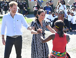The Duchess of Sussex joins in with dancers as she and the Duke of Sussex leave the Nyanga Township in Cape Town, South Africa, on the first day of their tour of Africa.