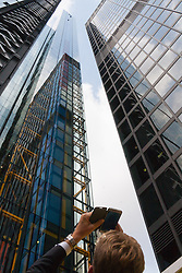 London, September 7th 2015. PICTURED: A passerby takes a picture with his phones as the tiny speck near the top of the tower, Bill Roberts of Clogau Goldmine abseils down the side of 20 Fenchurch Street. The Outward Bound Trust City Three Peaks Challenge in conjunction with The Royal Navy and Royal Marines Charity is a breathtaking abseiling endeavour on the greatest urban mountain range: The City of London.