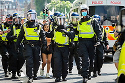 © Licensed to London News Pictures. 19/07/2021. LONDON, UK.  Police officers in Whitehall with an arrested protester at an anti-vaccine protest in Parliament Square, on what has been dubbed Freedom Day, when the UK government relaxed remaining coronavirus lockdown restrictions but the numbers of positive cases continues to increase daily and scientists concerned that restrictions have been eased too soon.  Photo credit: Stephen Chung/LNP